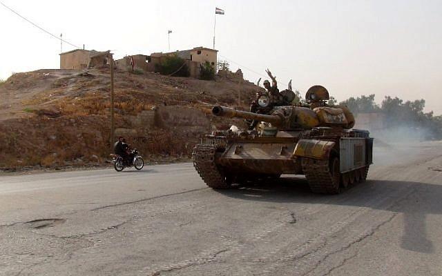 مقاتل موال للنظام يرفع إشارة النصر في 21 أغسطس، 2016 وهو يقود دبابة في حي غويران في مدينة السحكة، شمال شرق سوريا، حيث حققت القوات الكردية تقدما. (AFP/STR)
