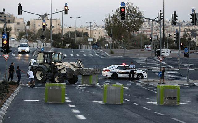 شرطي إسرائيلي يحرس حيث تضع قوات الأمن الإسرائيلية كتل إسمنتية على طريق يربط بين بيت حنينا والقدس الغربية بالقدس الشرقية في 11 أكتوبر / تشرين الأول 2016 قبيل يوم الغفران. (AFP/Ahmad Gharabli)