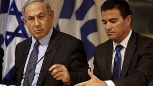 رئيس الوزراء بينيامين نتنياهو (من اليسار) يجلس إلى جانب يوسي كوهين في عام 2015. (AFP photo/Gali Tibbon)