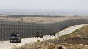 مركبات عسكرية إسرائيلية تسير على طريق مقابل للسياج الحدودي الذي يفصل الجانبين الإسرائيلي والسوري لمنطقة هضبة الجولان، 19 يوليو، 2017. (AFP/MENAHEM KAHANA)