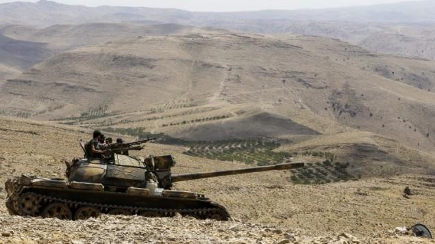 صورة تم التقاطها في 2 أغسطس، 2017، خلال جولة نظمتها منظمة 'حزب الله' الشيعية يظهر فيها عناصر من قوات النظام السوري يركبون دبابة في موقع في منطقة جبلية في محيط بلدة فليطة السورية بالقرب من الحدود مع لبنان. (AFP/LOUAI BESHARA)