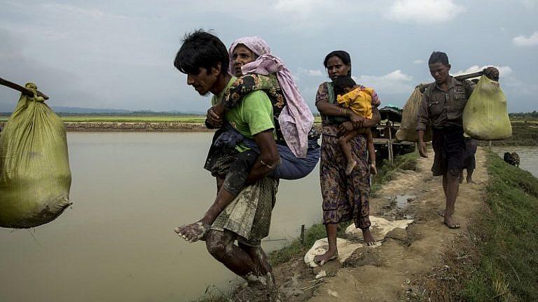 نزوح لاجئي الروهينغا من ولاية راخين في ميانمار سيرا على الأقدام بالقرب من أوخيا، على الحدود بين بنغلاديش وميانمارا، فرارا من أعمال العنف، في 4 سبتمبر 2017. (AFP/K.M. Asad)
