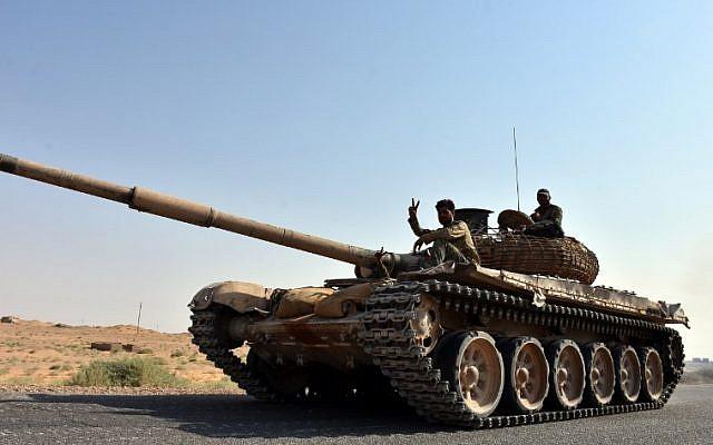 يرفع أفراد قوات الحكومة السورية بادرة الانتصار وهم يركبون دبابة في قرية كباجب على الضواحي الجنوبية الغربية لمقاطعة دير الزور، في 6 سبتمبر / أيلول 2017. (AFP/George OURFALIAN)