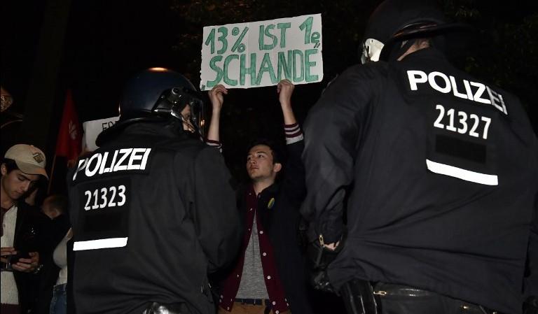 """متظاهر يحمل لافتة كُتب عليها '13 بالمئة هو عار"""" خلال تظاهرة أمام تجمع بمناسبة ليلة الإنتخابات لحزب 'البديل من أجل ألمانيا' في برلين بعد النتائج التشريعية في 24 سبتمبر، 2017. (AFP PHOTO / John MACDOUGALL)"""