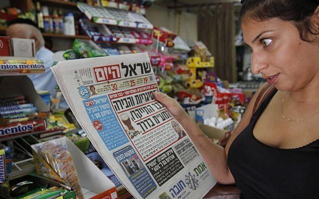 امرأة تقرأ صحيفة 'يسرائيل هيوم' (Miriam Alster/Flash90)