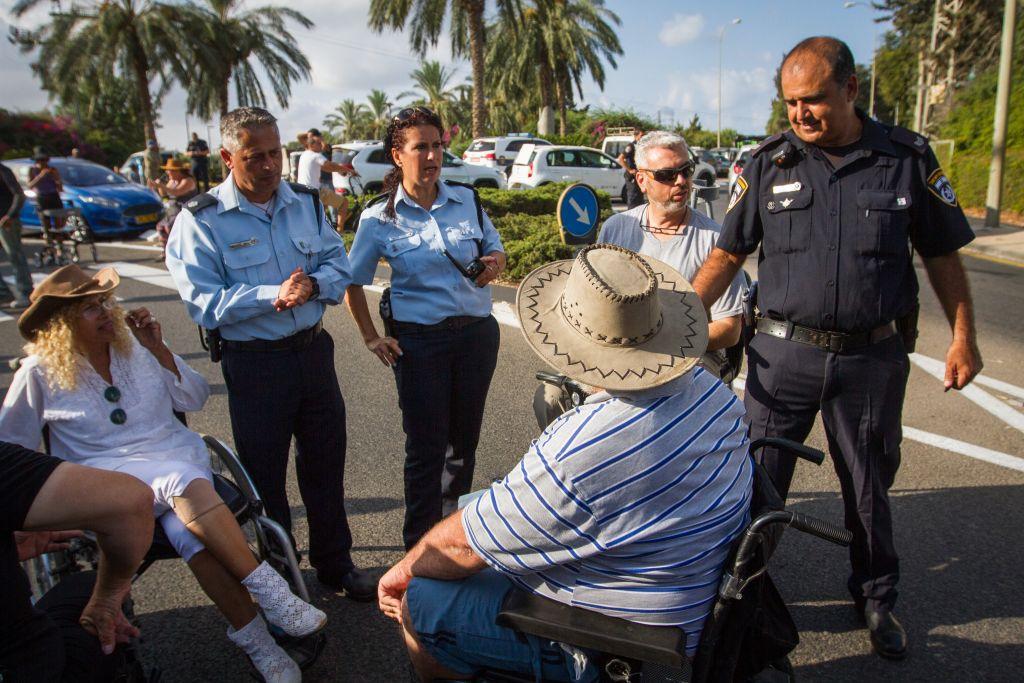 صورة توضيحية لنشطاء معاقين يقومون بإغلاق طريق خلال تظاهرة تطالب بزيادة مخصصات الإعاقة، على الطريق الرئيسي عند مدخل مدينة قيسارية، 28 أغسطس، 2017. (Flash90)