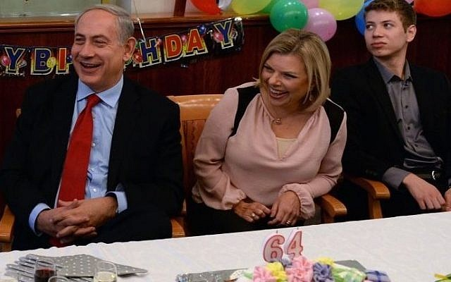 رئيس الوزراء بينيامين نتنياهو يجلس مع زوجته سارة ونجله يائير في حفل بمناسبة عيد ميلاده ال64 في مكتب رئيس الوزراء في عام 2013. (photo credit: Kobi Gideon/GPO)