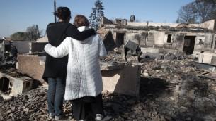 مستوطنون إسرائيليون ينظرون إلى منازلهم المحترقة في مستوطنة حلميش في 27 نوفمبر، 2016. ( AFP / MENAHEM KAHAN)