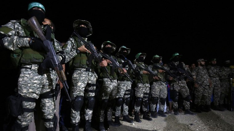 مقاتلون من 'كتائب عز الدين القسام'، الجناح العسكرية لحركة 'حماس'، يشاركون في مراسم تذكارية لأحد القادة الذي قُتل في في حادثة انفجار عرضي كما يبدو جنوب قطاع غزة، 10 يونيو، 2017.(AFP/Said Khatib)
