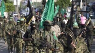 مسلحون فلسطينيون من 'كتائب عز الدين القسام'، الجناح المسلح لحركة 'حماس' الفلسطينية، يشاركون في مسيرة عسكرية مناهضة لإسرائيل في مدينة غزة، 25 يوليو، 2017. ( AFP PHOTO / MAHMUD HAMS)