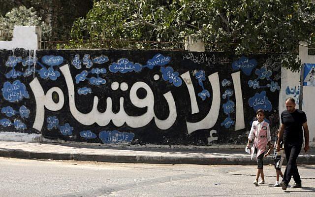 رجل فلسطيني وطفلتيه يمران من أمام رسم غرافيتي كُتب عليه بالعربية 'الإنقسام' في مدينة غزة، في 17 سبتمبر، 2017، بعد أن أعلنت حركة 'حماس' عن موافقتها على خطوات للسماح بحل النزاع مع حركة 'فتح' المستمر منذ عقد من الزمن واستعدادها لإجراء انتخابات. (AFP/Mahmud Hams)