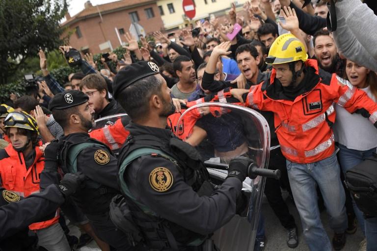 رجال إطفاء يحاولون منع مجموعة من المحتجين من مواجهة عناصر الحرس المدني الإسباني خارج محطة إقتراع في سان يوليا دي راميس، 1 أكتوبر، 2017، في اليوم الذي أجري فيه الإستفتاء على إستقلال كاتالونيا واعتبرته مدريد غير قانوني. (/ AFP PHOTO / LLUIS GENE)