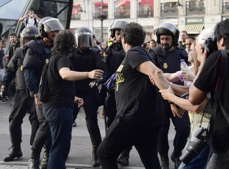 بعض المحتجين المؤيدين يواجهون الشرطة الإسبانية خلال مواجهات في ميدان 'بويرتا ديل سول' لإجراء الإستفتاء على حق تقرير المصير في كاتالونيا وضد القمع، في مدريد، 1 أكتوبر، 2017. (AFP PHOTO / JAVIER SORIANO)