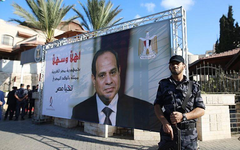مقاتل من حركة 'حماس' يقف إلى جانب يافطة تحمل صورة للرئيس المصري عبد الفتاح السيسي بالقرب من مقر الحكومة في مدينة غزة، 3 أكتوبر، 2017. (AFP Photo/Mohammed Abed)