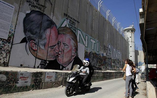 سياح امام جدارية للفنان لاشساكس تظهر اللرئيس الامريكي دونالد ترامب بتبادل القبل مع رئيس الوزراء الإسرائيلي بنيامين نتنياهو على الجدار الفاصل بين مدينة بيت لحم في الضفة الغربية ومدينة القدس، 29 اكتوبر 2017 (AFP PHOTO / Musa AL SHAER)