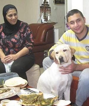 سليم شريف وأمه في منزلهم مع كلب الارشاد ونستون. (Courtesy)