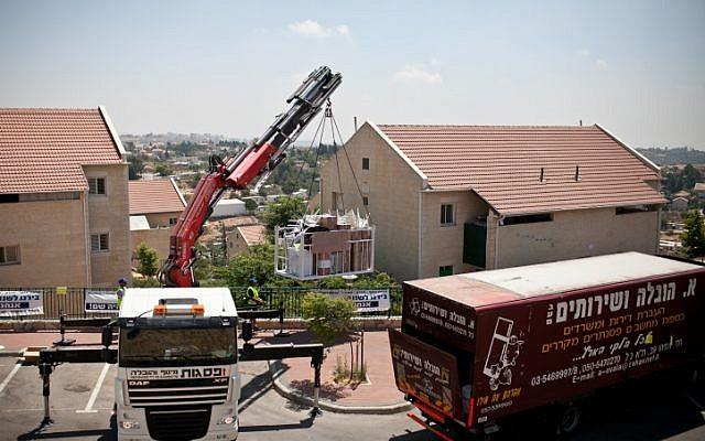 عمال من وزارة الدفاع يبدؤون صناديق وأثاث خارج منازل بؤرة أولبانا الإستيطانية في مستوطنة بيت إيل، 26 يونيو، 2012.( Noam Moskowitz/Flash90)