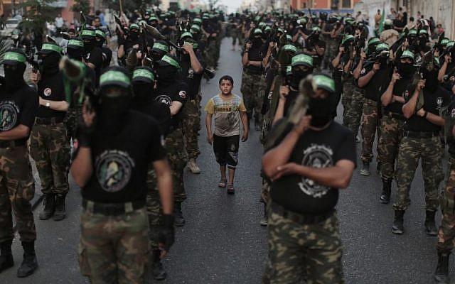عناصر من 'كتائب عز الدين القسام'، الجناح المسلح لحركة 'حماس'، خلال مسيرة مناهضة لإسرائيل في إطار إحياء الذكرى الأولى لعملية عسكرية إسرائيلية في غزة، 14 نوفمبر، 2013. (Wissam Nassar/Flash90)
