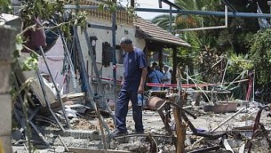رجل يتفقد الأضرار لمنزل بعد هجوم صاروخي من قطاع غزة على بلده يهود الإسرائيلية، القريبة من مطار بن غوريون الدولي، 22 يوليو، 2014. (Yonatan Sindel/Flash90)