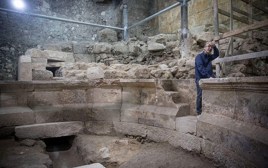 يقوم جو عوزيئيل، وهو عالم آثار في سلطة الاثار الإسرائيلية، بتنظيف الحجارة في موقع هيكل روماني قديم يشبه المسرح، كان مخفيا منذ 1700 سنة، ومتصل بشكل مباشر بالجدار الغربي تحت البلدة القديمة في القدس في 16 أكتوبر 2017. (Yonatan Sindel/Flash90)