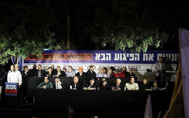 نواب وممثلون للعائلات الثكلى وقادة مستوطنين يجلسون على المنصة خلال مظاهرة أمام منزل رئيس الوزراء مطالبين بتحويل أموال لتعبيد شوارع إلتفافية في الضفة الغربية، 29 أكتوبر، 2017. (Noam Revkin Fenton/Flash90)