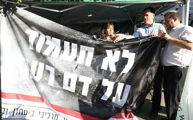رئيس المجلس الإقليمي يوسي دغان (من اليمين) يعلق لافتة كُتب عليها 'لا تقف مكتوف الأيدي أمام سفك دماء جارك' في خيمة اعتصام خارج مقر إقامة رئيس الوزراء في القدس، 24 أكتوبر، 2017. (Courtesy: Miri Tzachi)