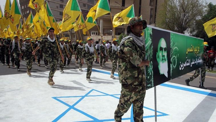 صورة للتوضيح: عناصر عراقية تابعة ل'حزب الله' تحمل أعلاما صفراء للفرع العراقي للمنظمة اللبنانية وصورة للمرشد الأعلى الإيراني السابق، آية الله روح الله خامنئي، وتسير على علم إسرائيلي مرسوم على الأرض خلال مسيرة لإحياء 'يوم القدس العالمي' في 25 يوليو، 2014، في العاصمة العراقية بغداد. (AFP/Ali al-Saadi)