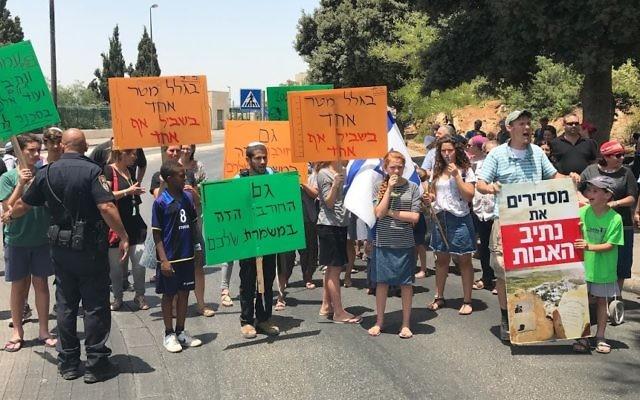 سكان نتيف هآفوت في مظاهرة احتجاجا على قرار المحكمة العليا بهدم 17 مبنى في بؤرتهم الاستيطانية أمام الكنيست، 17 يوليو، 2017. (Jacob Magid/Times of Israel)