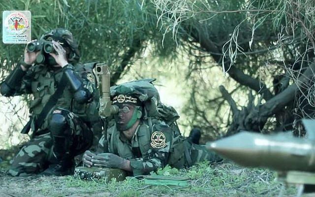 صورة شاشة من فيديو اصدره الجهاد الإسلامي يظهر اعضاء الحركة يجهزون صاروخ لاطلاقه ضد القوات الإسرائيلية على حدود قطاع غزة (YouTube/alquds Brigades)