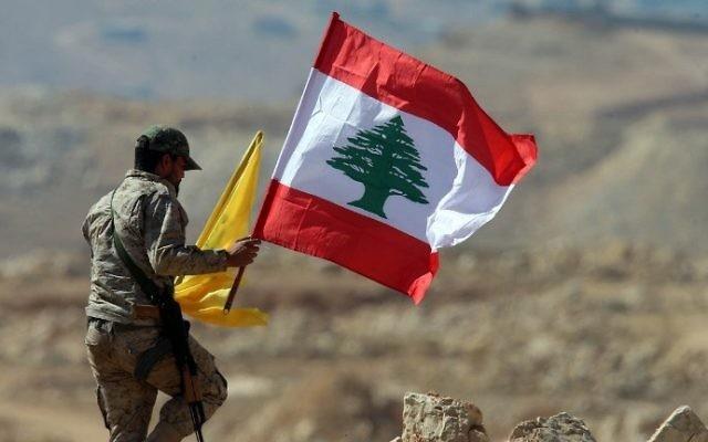 """أحد عناصر منظمة """"حزب الله"""" اللبنانية يحمل العلم اللبناني وعلم 'حزب الله' خلال جولة للصحافيين بالقرب من مدينة عرسال الحدودية، 25 يوليو، 2017. (AFP Photo/Stringer)"""