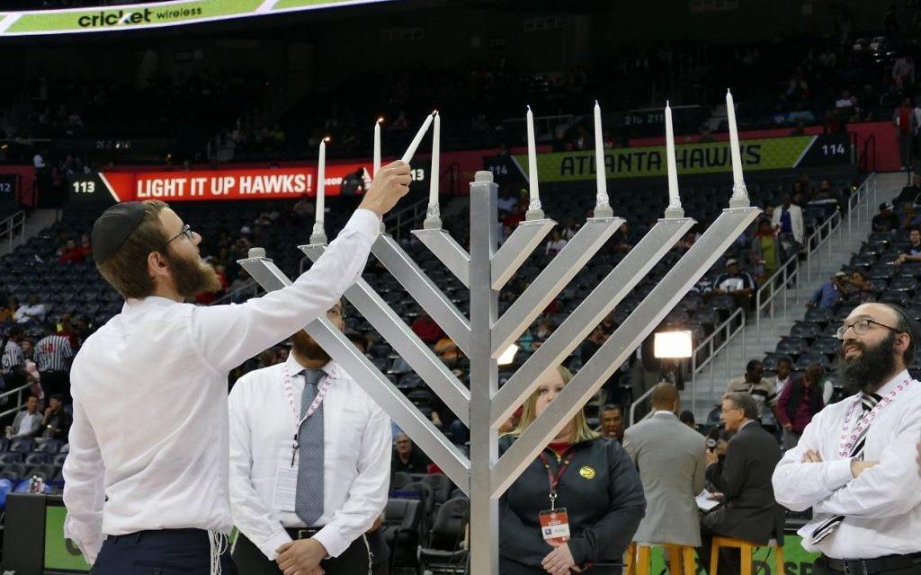 Menachem Loebenstein lights the menorah while Rabbi Isser New looks on.