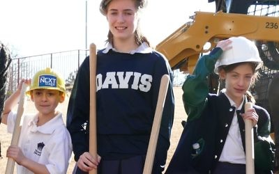Second-grader Benjamin Barkan, eighth-grader Abigail Barkan and fifth-grader Miriam Barkan, representing the present and future of the Davis Academy and the Davis family, get their turn with the shovels at the groundbreaking.