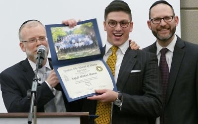Rabbi Shimon Wiggins (left) and Rabbi Yechezkel Freundlich flank new graduate Naftali Maman.