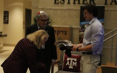 Student activities director at Texas A&M Hillel Weber School graduate and Texas A&M kinesiology sophomore Joshua Williams presents Aggie gear to Holocaust survivors Thomas Gabor and his wife, Danielle.