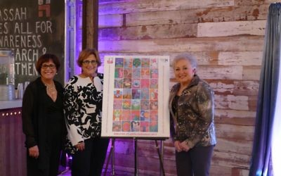 Big Reveal chair Janis Greenfield and Breast Strokes co-chairs Linda Hendelberg and Linda Weinroth stand with a poster of this year's art.