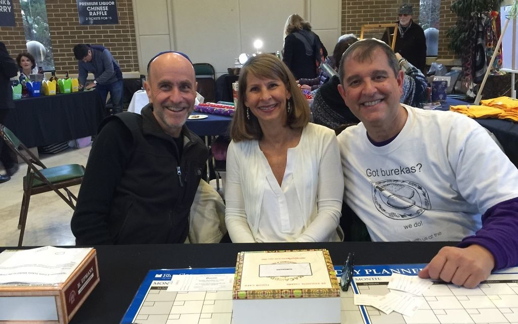 The lay leaders of three of Jewish Atlanta's biggest nonprofits, Joel Marks of Federation (left), Deborah Maslia of Jewish Home Life Communities and Joel Arogeti of the Marcus JCC, staff the entrance desk at the OVS Chanukah bazaar in December 2016