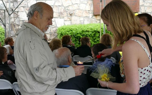 A NFTY member lights a memorial candle for a survivor at the Memorial to the Six Million during the annual Yom HaShoah service in 2017.