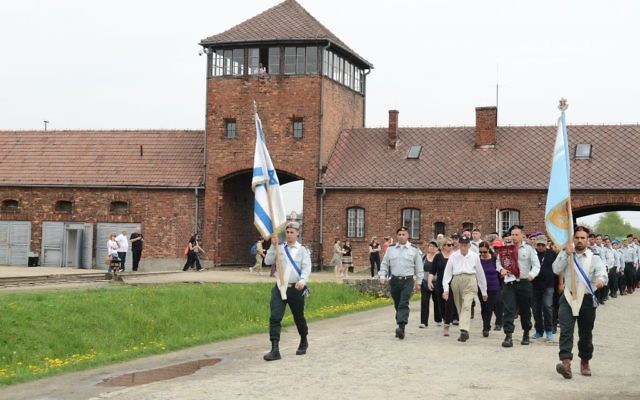 Yaakov Selavan carries the Torah to lead an IDF delegation into Auschwitz-Birkenau.