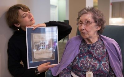 """Eli Abeita (left) and Dian Biddle look at a photograph called """"The Bakery Story"""" by Ori Salzberg."""