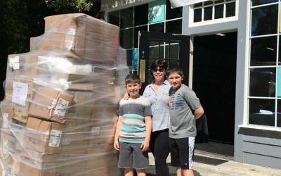 Harrison Frank, with his mom, Wendy, and one of his brothers, Avi, brings a donation of gift items to the Packaged Good.