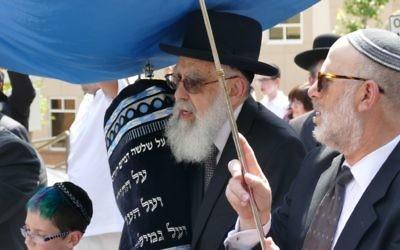 Rabbi Emanuel Feldman carries the new Torah into Beth Jacob.