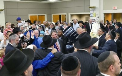 Nearly an hour of dancing with the shul's Torahs in Heritage Hall follows the parade along Breezy Lane.