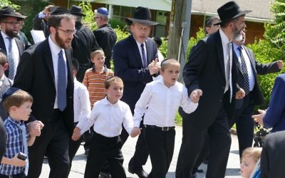 Beth Jacob members, including Rabbi Ilan Feldman, dance their way along Breezy Lane to bring the new Torah home.