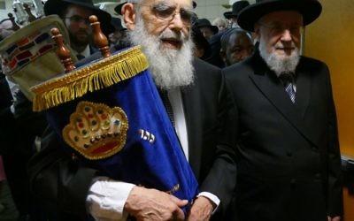 Accompanied by Rabbi Israel Meir Rau, Rabbi Emanuel Feldman carries one of Beth Jacob's Torahs from Heritage Hall to the new sanctuary.