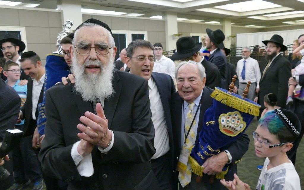 Congregation Beth Jacob Rabbi Emeritus Emanuel Feldman is joined by Atlanta Scholars Kollel Rabbi David Silverman and past shul President Bob Maran at the center of the Heritage Hall dancing to celebrate the completion of a new Torah on July 9.