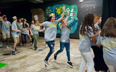 Photo by Andria Lavine Photography Sporting Waffle House-style shirts and hats, members of the Weber School Class of 2018 charge into the basement theater to celebrate the first day of their last year of high school Aug. 14.