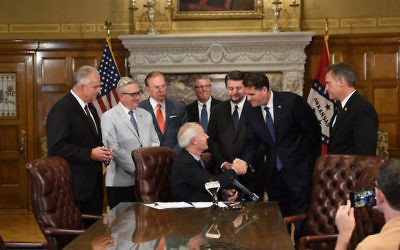 Arkansas Gov. Asa Hutchinson (seated) is congratulated by Ambassador Ron Dermer after signing a pair of pro-Israel bills Aug. 14.