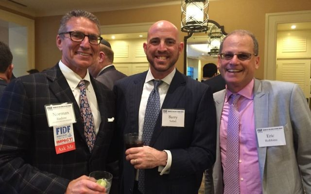 Norman Radow (left), whose philanthropy includes Friends of the Israel Defense Forces, socializes with Barry Sobel and Federation CEO Eric Robbins during the annual FIDF dinner in May 2017.