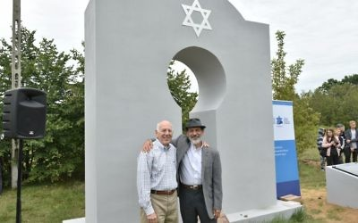 Ed Goldberg of Atlanta (left) and Mark Upfal of Ann Arbor, Mich., stand in front of the memorial monument in the cemetery in Kaluszyn.