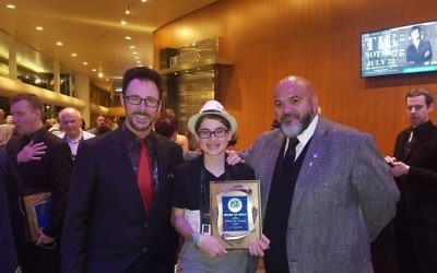 Magician Lance Burton and International Brotherhood of Magicians President Oscar Munoz congratulate Ari Slomka for finishing second in the North American close-up magic championship.